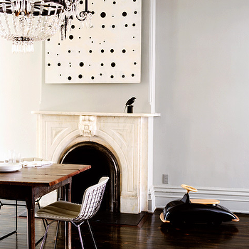 Domino Magazine - dining rooms - limestone fireplace, dining room fireplace, art over fireplace, rustic dining table, metal dining chairs, gray walls,