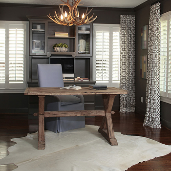 Ashley Goforth Design - dens/libraries/offices - cowhide rug, white cowhide rug, trestle desk, purple chair, purple desk chair, purple slipcovered chair, black and white curtains, black and white drapes, geometric curtains, geometric drapes, pelagos curtains, pelagos drapes, faux antler chandelier, dark gray built ins, dark gray built in cabinets, office built ins, office built in cabinets, Windsor Smith Pelagos Fabric,