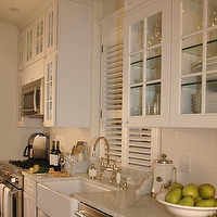 Paul Corrie Interiors - kitchens - stainless steel appliances, kitchen cabinets with glass fronts, glass front cabinets, glass front kitchen cabinets, louvered windows, farmhouse sink, white apron sink, carrera marble, carrera marble countertops, white cabinets, glass front kitchen cabinets, long kitchen, microwave over range,