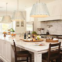 Thornton Designs - kitchens - pleated pendants, pleated light pendants, silver pleated pendants, kitchen island with legs, long kitchen island, white kitchen cabinets, paneled range hood, white marble countertops,