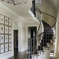 Grand luxurious entry foyer design with curved staircase, white & black stair runner, ...