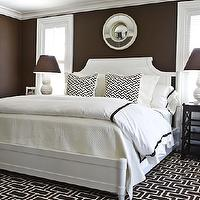 Phoebe Howard - bedrooms - brown walls, brown paint, brown paint color, white and brown bedroom, brown lamp shades, white bed, white headboard, brown rug, geometric rug, brown geometric rug, espresso nightstands, white lamps with brown shades,
