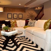 basements - nate rug, botanicals, ikat pillows, west elm mirror, overstock art, coffee table, glass top coffee table, chevron rug, slipcovered sectional, white slipcovered sectional, mega greige, basement family room,