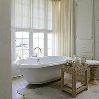 bathrooms - grasslcoth table, grasscloth accent table, white cowhide rug, freestanding bathtub, cream sheers, cream sheer curtains,  Antoine