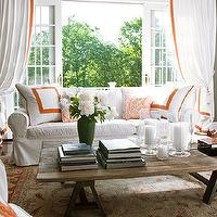 Traditional Home - living rooms - Mitchell Gold + Bob Williams, white, slipcovered, sofa, gray, walls, rustic, sawhorse, coffee table, white, drapes, orange, trim, glass hurricanes, Mitchell Gold, Mitchell Gold sofa,