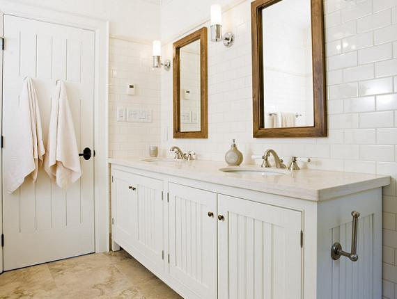 bathrooms - white bathroom beadboard cabinets marble countertops rustic wood mirrors double sinks subway tiles backsplash polished nickel sconces stone tiles floor