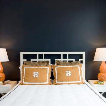 Sally Steponkus Interiors - bedrooms - x table, x nightstand, white x table, white x nightstand, orange lamps, orange gourd lamp, orange shams, white headboard, overlapping squares headboard, white overlapping squares headboard, navy blue walls, navy accent wall, navy blue accent wall, bedroom accent wall, navy and orange bedroom, navy blue and orange bedroom,