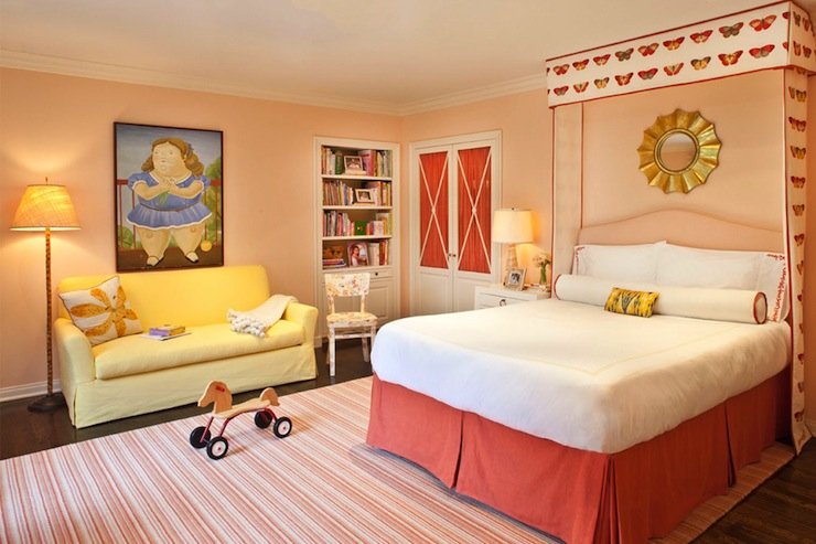 girl's rooms - pink walls pink camelback headboard butterfly fabric cornice box coral bed skirt pink white striped rug yellow slipcovered sofa built-ins bookshelf gold sunburst mirror
