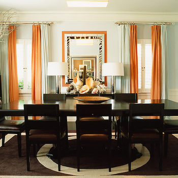 Mary McDonald - dining rooms - orange drapes, orange curtains, orange window panels, zebra mirror, espresso dining table, dark brown dining table,