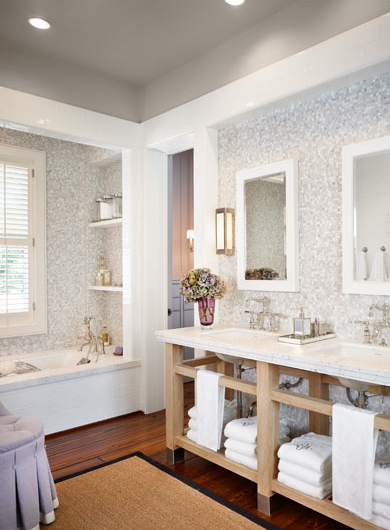 bathrooms - gray walls gray mosaic tiles backsplash shower surround wood washstand calcutta marble countertops double sinks polished nickel faucets sconces sisal rug lilac purple round skirted tufted ottoman white mirrors soaking tub