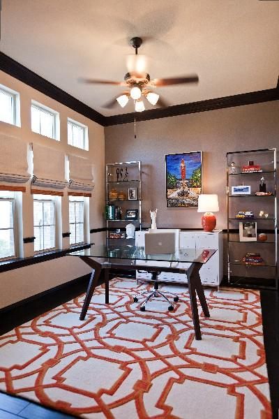 dens/libraries/offices - Arabesque Rug-Coral taupe gray walls modern chic polished nickel bookshelves towers glass-top desk linen roman shades orange ribbon trim