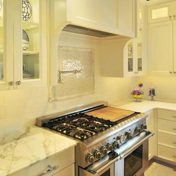 Beckwith Interiors - kitchens - two tone countertops, island with two countertops, white kitchen cabinets, glass front kitchen cabinets, calcutta marble countertops, calcutta marble backsplash, paneled range hood, mosaic cooktop backsplash,