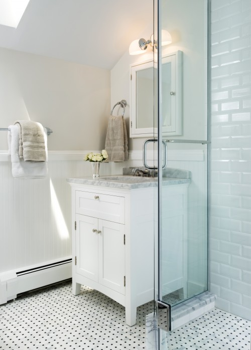 bathrooms - skylight greige walls subway tiles shower surround frameless glass shower marble basketweave tiles floor white bathroom cabinet vanity glass knobs white carrara marble countertop white medicine cabinet mirror polished nickel sconces faucet chair rail beadboard