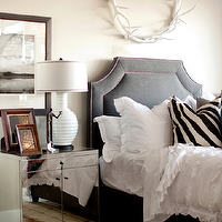 Ashlee Raubach Photography - bedrooms - charcoal, headboard, bed, red, purple, nailhead trim, white, ruffled, bedding, white, black, zebra, pillows, white, ribbed, lamp, tan, walls, white, horns, round, circle, wall decor, mirror nightstand, mirrored nightstands, Oly Studio Antler Wreath, Oly Studio Eva Bedside Table,