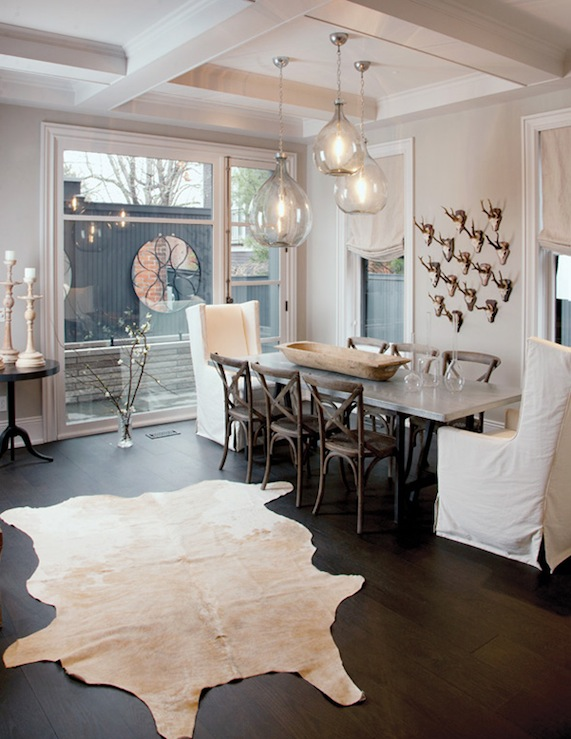 dining rooms - iron trestle dining table marble top canvas slipcovered wingback captain chairs French x-back cafe chairs white cowhide rug fray walls coffered ceiling glass tear drops pendants chandelier