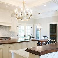Tiek Built Homes - kitchens - two tone countertops, 2 tone countertops, raised breakfast bar, butcher block countertops, wood countertops, wood kitchen countertops, white marble, white marble countertops, kitchen island chandelier, paneled kitchen hood, paneled range hood, coffered ceiling,