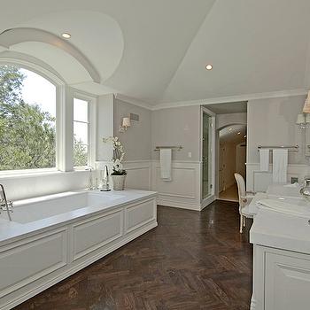 bathrooms: herringbone wood floors, herringbone bathroom floor, wood herringbone floor, wainscoting, bathroom wainscoting, wainscoting in bathroom, soaking tub, paneled bathtub,