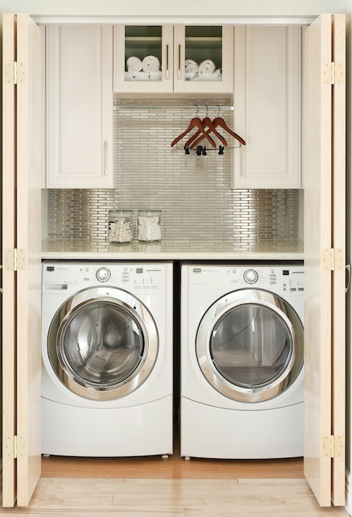 At Home in Arkansas - laundry/mud rooms - white, washer, dryer, stainless steel, linear, tiles, backsplash, ivory, cabinets, folding doors,