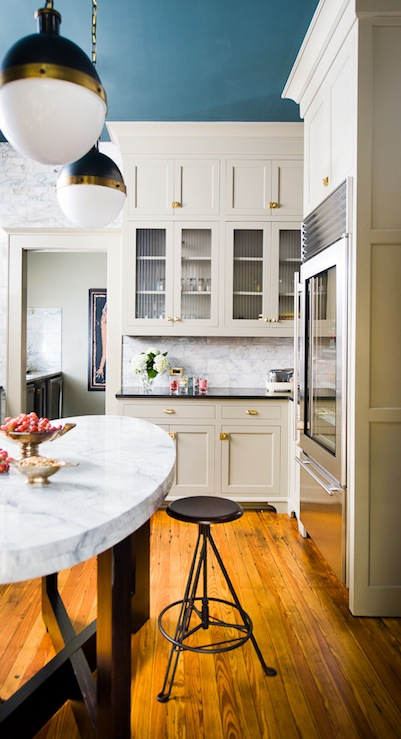 David Christensen Photography - kitchens - Thomas O'Brien Hicks Pendant, oval kitchen island, oval center island, light gray cabinets, light gray kitchen cabinets, gray cabinets with brass hardware, gray kitchen cabinets with brass hardware, glass front fridge,
