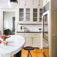 David Christensen Photography - kitchens - oval kitchen island, oval center island, light gray cabinets, light gray kitchen cabinets, gray cabinets with brass hardware, gray kitchen cabinets with brass hardware, glass front fridge, Thomas O'Brien Hicks Pendant,