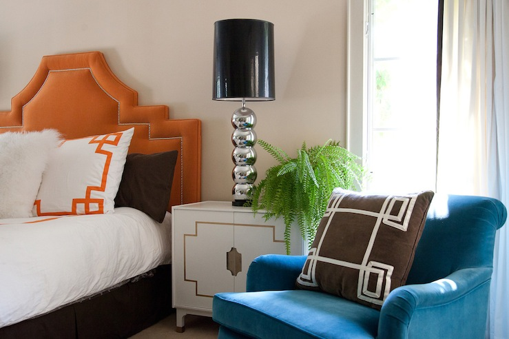 bedrooms - orange headboard nailhead trim blue velvet chair brown pillow white Greek key trim vintage white lacquer Hollywood Regency nightstand polished chrome stacked balls lamps black vinyl lamp shades brown pillows white bedding orange Greek key trim