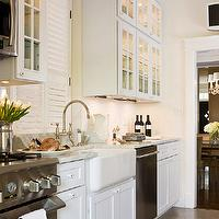 Paul Corrie Interiors - kitchens - farmhouse sink, ivory, walls, flatscreen tv, white, glass-front, kitchen cabinets, white, carrara, marble, countertops, polished nickel, gooseneck, faucet, galley kitchen, white galley kitchen, traditional galley kitchen, galley kitchen design, galley kitchen cabinets, white galley cabinets, white galley kitchen cabinets, glass front galley cabinets, glass front galley kitchen cabinets,