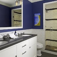 Cute boys' bathroom design with bold blue walls paint color, subway tiles backsplash, ...