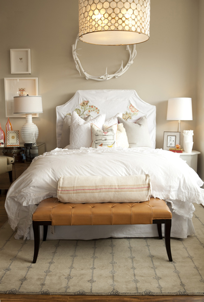 bedrooms - Serena Drum Chandelier Oly Studio Antler Wreath caramel leather tufted bench white slipcovered headboard bed crisp white ruffled bedding tan walls mirrored nightstand mismatched nightstands