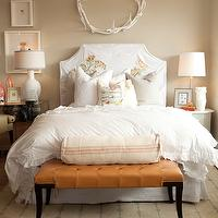 bedrooms - caramel leather tufted bench white slipcovered headboard bed crisp white ruffled bedding tan walls mirrored nightstand mismatched nightstands
