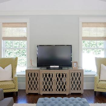 Caitlin Creer Interiors - living rooms - blue green walls, blue green paint, blue green paint colors, blue tufted ottoman, blue ottoman, yellow chairs, yellow wingback chairs, media cabinet, big sur cabinet, , Worlds Away Big Sur Cabinet, F Schumacher Ziggurat Chartreuse, CB2 Big Dipper Arc Lamp,