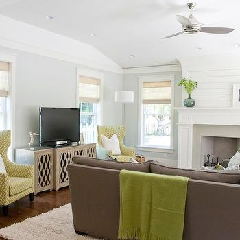 Caitlin Creer Interiors - living rooms - blue green walls, blue green paint, blue green paint colors, gray sofa, blue tufted ottoman, blue ottoman, taupe sectional, taupe sectional sofa, yellow chairs, yellow wingback chairs, media cabinet, bali grass blinds in coronado white sand, F Schumacher Ziggurat Chartreuse, Worlds Away Big Sur Cabinet, West Elm favorite Throw in Bean Sprout,