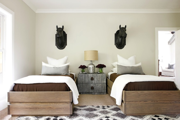 boy's rooms - tan walls glossy black horse head wall sculptures Bungalow Classics wood twin beds brown bedding gray lumbar pillows gray graphic diamonds rug gray chest green vases