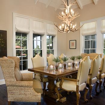 Light filled Dining Room with wing captain chairs and antler chandelier