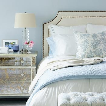Muse Interiors - bedrooms - mirror nightstands, mirrored nightstands, mirrored bedside tables, antique mirrored nightstand, antiqued mirrored nightstand, ivory headboard, studded headboard, tufted bench, blue blanket,