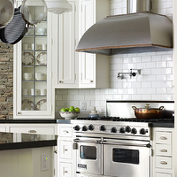 Linda Ruderman Interiors - kitchens - stainless steel, range hood, pot filler, beadboard, ceiling, ivory, kitchen cabinets, ivory, beadboard, kitchen island, white, subway tiles, backsplash, brick, wall, Absolute Black, granite, countertops, copper, pot rack,