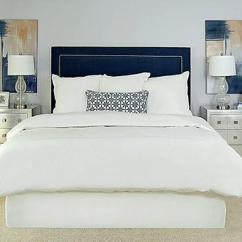 EJ Interiors - bedrooms: Upholstered blue headboard with nailheads, abstract art, metallic nightstands, navy, gray, purple, geometric pillow, white bedding, gray-purple walls, Restoration Hardware bedding, Home Goods lamps, artichoke accessory, king bed, silver nightstands,