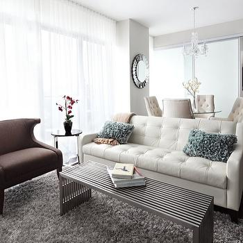LUX Design - living rooms - media cabinet, white media cabinet, quatrefoil wallpaper, silver wallpaper, silver quatrefoil wallpaper, metal coffee table, gray flokati rug, brown wingback chair, white tufted sofa,