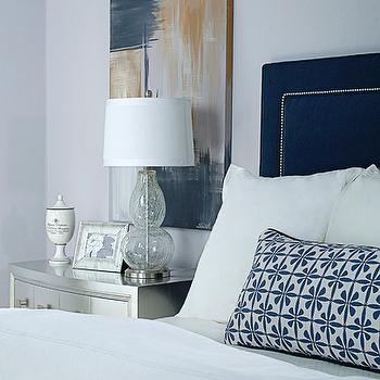 EJ Interiors - bedrooms - Abstract art, glass lamp, metallic silver nightstand, navy upholstered headboard, purple-gray walls, white bedding, velvet headboard, blue velvet headboard, nailhead trim headboard, nailhead headboard, headboard with nailhead trim,