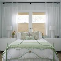 Rethink Design Studio - bedrooms - green, iron, bed, green, greek key, pillow, pale, blue, paneled, walls, glossy, white, lamps, white, chests, nightstands, be din front of window,