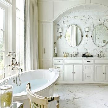 Atlanta Homes & Lifestyles - bathrooms: freestanding, oval, tub, white, built-in, double, bathroom cabinets, double sinks, marble, backsplash, tiles, oval, pivot mirror, ivory, green, velvet, Greek key, fabric, French, chair, white, silk, drapes, black, Greek key, ribbon, trim, sink alcove, bathroom sink alcove, bathroom chair, tub in front of window, bathroom in front of window,