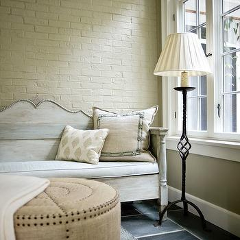 Atlanta Homes & Lifestyles - living rooms - exposed brick wall, painted, yellow, white, washed, settee, iron, floor, lamp, burlap ottoman, bulls eye ottoman, studded burlap ottoman, wood settee, Burlap Bullseye Ottoman,