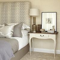 Gray bedroom design with tall headboard upholstered in shades of gray silk fabric, ...