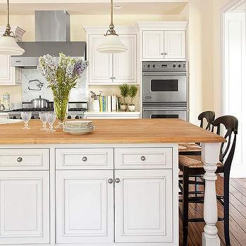 BHG - kitchens - white, raised panel, kitchen cabinets, marble, countertops, cooktop, backsplash, white, kitchen island, baluster, legs, butcher block, countertop, double ovens, coffered ceiling, kitchen island with carved legs, center island with carved legs, Pottery Barn Napoleon Barstool,