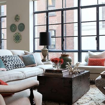Chic city living room with ivory sofa & chairs, espresso satined trunk cocktail ...