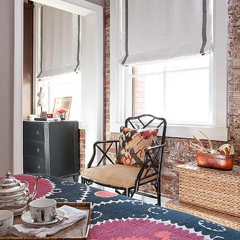Jenny Wolf Interiors - bedrooms - gray, walls, exposed brick wall, woven, stacked, baskets, suzani, blanket, black, chest, white, roman shade, charcoal, gray, ribbon, trim, suzani rug, Ballard Designs Macau Armchair,