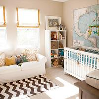 Beautiful boy's nursery design with tan walls paint color, white rolled-arm slip-cover ...