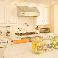 Modern Declaration - kitchens - white, oval, marble, top, kitchen island, pot filler, ivory, walls, orange, leather, counter stools, white, shaker, kitchen cabinets, marble, countertops, marble, slab, backsplash, ring, pulls, hardware,