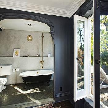 bathrooms: black, walls, arched, doorway, black, claw foot, tub, brass, shower kit, wood, herringbone, pattern, floors, French, doors, bathroom alcove, bathing alcove,