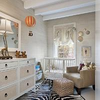 Chic gray nursery design with gray grasscloth wallpaper, oval white crib, mushroom linen ...