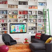 Jennifer Eisenstadt - media rooms - orange, ombre, rug, acrylic, round, accent table, fuchsia, Moroccan, leather, pouf, wall, white, modern, built-ins, bookshelves, green, ladder, TV, yellow, red, green, pillows, Room & Board Jasper Sectional Sofa with Chaise Lounge, Saarinen Womb Chair, CB2 Peekaboo Clear Coffee Table,
